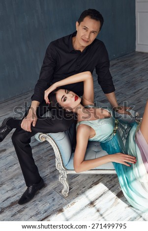 Beautiful couple in love brunette girl with long hair red lipstick and jewelery naked hugs sexual brutal handsome man in a black shirt and suit tenderness and passion window shadow dress - stock photo