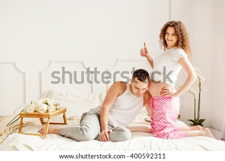 Beautiful couple in love in the bedroom. She is pregnant and standing on the bed. The man sitting next to the bed. He put his ear to her belly and listening to the child. Both dressed in home clothes. - stock photo