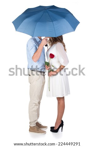 Beautiful couple in love kissing under umbrella, isolated on white background - stock photo