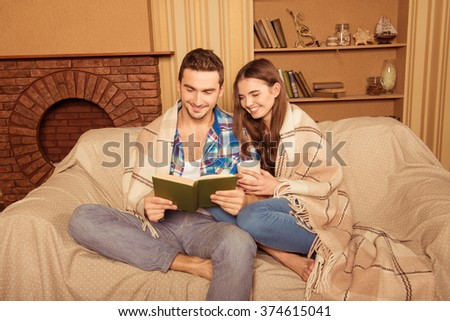 Beautiful couple in love reading book sitting in plaid