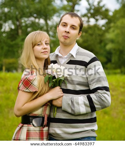 beautiful couple in love with flower against park