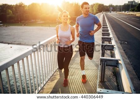 Beautiful couple in motion running over bridge - stock photo