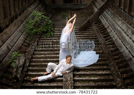 beautiful couple in old boat in wedding dress - stock photo
