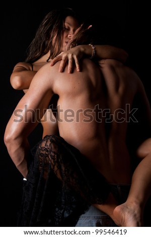 beautiful couple in passionate embrace and undressing each other during sexual foreplay - stock photo