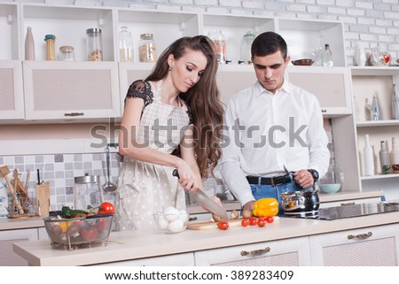 Beautiful couple in the kitchen preparing dinner, a man helps his wife