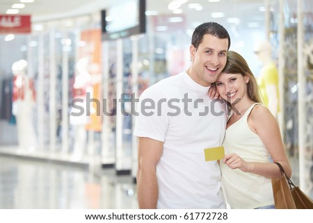 Beautiful couple in the store with credit card - stock photo