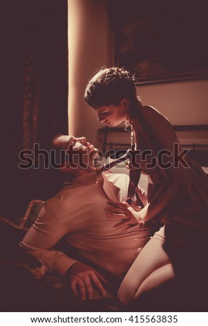 Beautiful couple is flirting in the bedroom. Retro styled toning. - stock photo