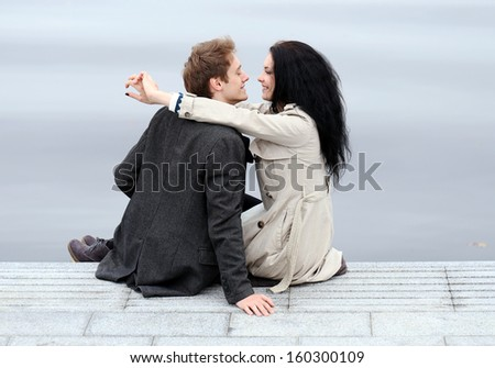 Beautiful couple is posing and showing their love to each other while hanging outdoors - stock photo