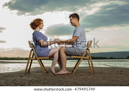 Beautiful couple is sitting on the chairs on the river background.