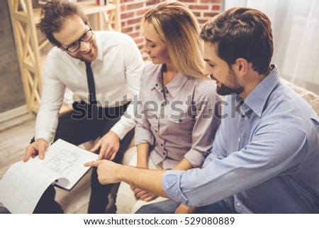 Beautiful couple is talking with handsome realtor in suit, examining drafts and smiling while sitting on couch at home