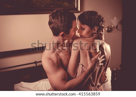 Beautiful couple is undressing in the bedroom. Retro styled toning. - stock photo
