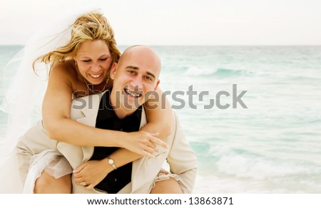 Beautiful couple just get married on the beach and having some fun - stock photo