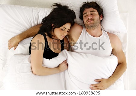 Beautiful couple laid asleep cuddling in the morning in a white bed