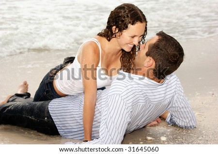 Beautiful couple laying on the beach looking into each others eyes, smiling and happy. - stock photo