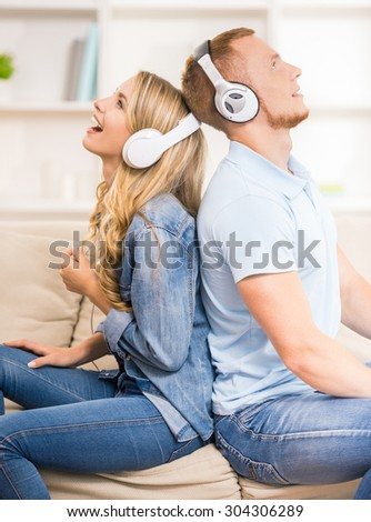 Beautiful couple listen to music with headphones while sitting back to back at home on the sofa.