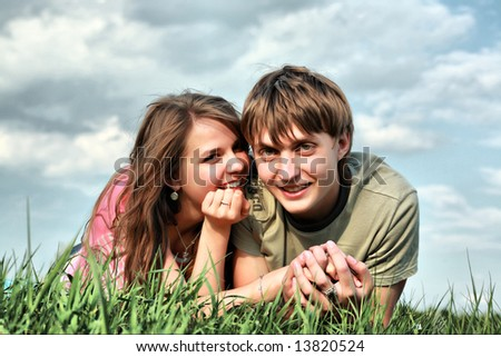Beautiful couple lying on the grass - stock photo