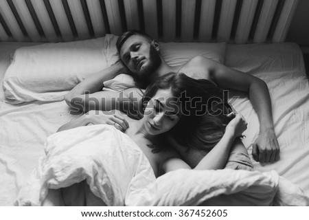 beautiful couple lying together on the bed - stock photo
