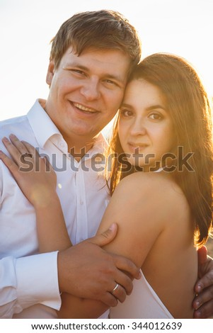 Beautiful couple man and woman rests together on a beach in a summer evening