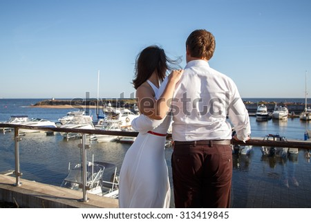 Beautiful couple man and woman walks together near yacht in a summer day