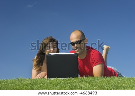 Beautiful couple of boyfriends having fun with a laptop - stock photo