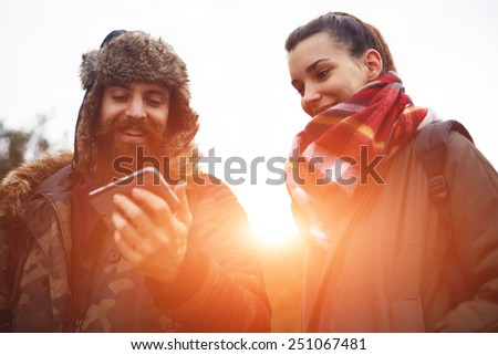 Beautiful couple of hikers laughing while looking to the mobile screen, young couple of backpackers enjoying a day out in nature together - stock photo