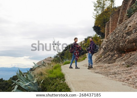 Beautiful couple of hikers walking on the trail with beautiful horizon view from altitude, couple hiking on a mountain trail together - stock photo