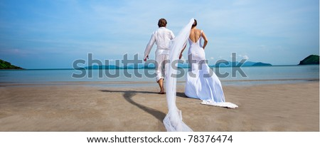 beautiful couple on the beach in wedding dress - stock photo