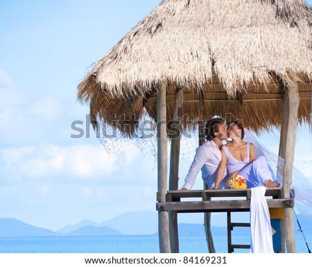 beautiful couple on the beach in wedding dress - stock photo