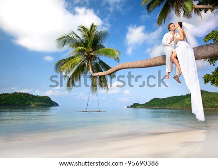 beautiful couple on the beach in wedding dress on palm tree - stock photo