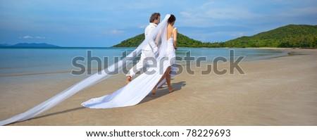 beautiful couple on the beach in wedding dress running - stock photo