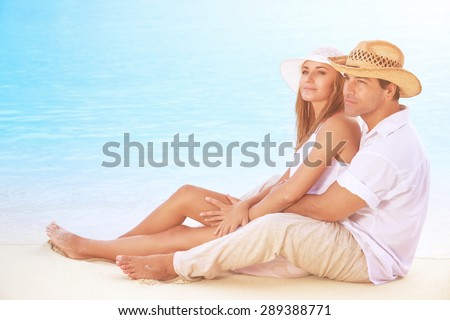 Beautiful couple on the beach, sitting on the coast and hugging, enjoying peaceful sunny day on tropical resort, romantic summer vacation  - stock photo