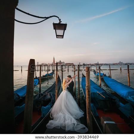 Beautiful couple on the pier among gondolas - stock photo