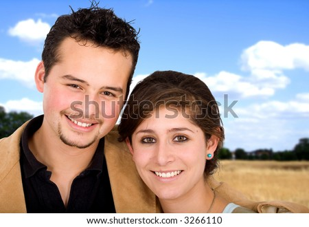Beautiful couple outdoors in a field during summer time