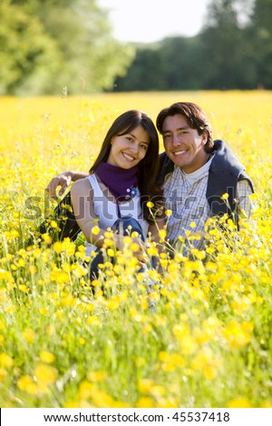 Beautiful couple outdoors in a meadow smiling - stock photo