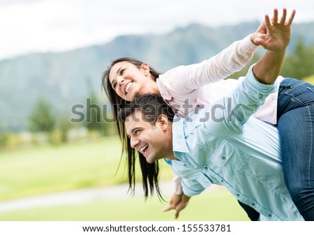 Beautiful couple outdoors with arms open like flying  - stock photo