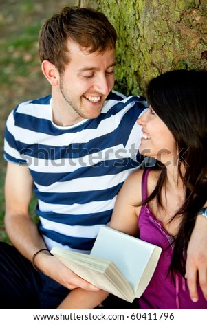 Beautiful couple portrait leaning on a tree with a book and smiling