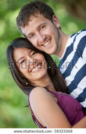 Beautiful couple portrait smiling outdoors - stock photo