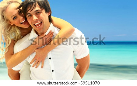 beautiful couple posing on the sandy sea coast - stock photo