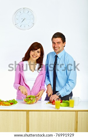 Beautiful couple preparing a salad for lunch in the kitchen - stock photo