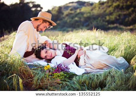 Beautiful couple relaxing in a field wearing historical costumes - stock photo