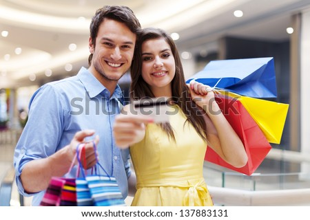 Beautiful couple showing credit card in the shopping mall - stock photo