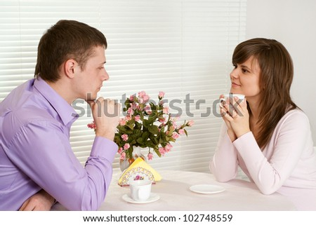 Beautiful couple sitting at a table drinking coffee on a light background - stock photo