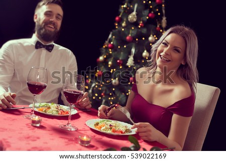 Beautiful couple sitting at a table, having a romantic Christmas dinner and enjoying their time together.