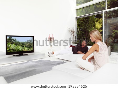 Beautiful Couple Sitting On Couch Watching TV - stock photo