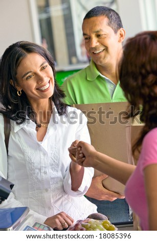 Beautiful couple smiling - a supermarket checkout with shopping till in a market - stock photo
