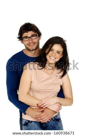 Beautiful couple smiling at the camera cuddling isolated on a white background - stock photo