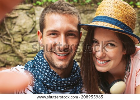 Beautiful couple smiling in your home garden./ Selfie photo of a young couple enjoying day in outdoors.  - stock photo