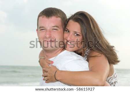 Beautiful couple smiling with each other at the beach