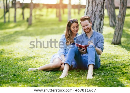 Beautiful couple studying together for exams in nature