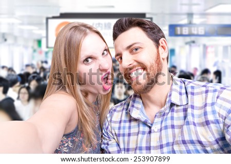 Beautiful Couple taking a selfie photo in Tokyo Subway, Japan  - stock photo